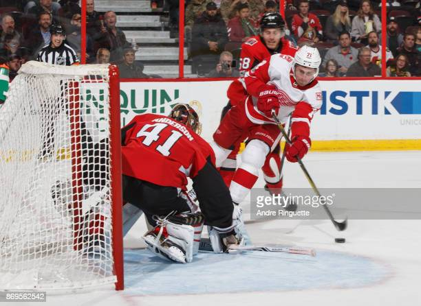 Dylan Larkin of the Detroit Red Wings drives to the net with the puck on a penaltykill as Craig Anderson and Mike Hoffman of the Ottawa Senators...