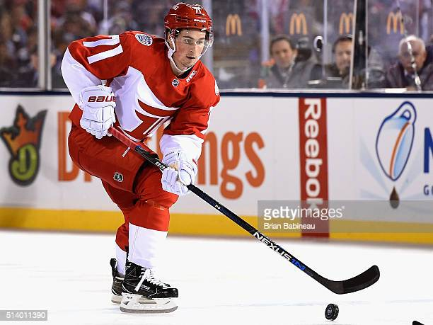 Dylan Larkin of the Detroit Red Wings plays the puck during the 2016 Coors Light Stadium Series game against the Colorado Avalanche at Coors Field on...