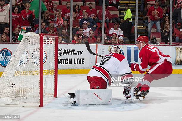 Dylan Larkin of the Detroit Red Wings scores his first goal of the year on Cam Ward of the Carolina Hurricanes during an NHL game at Joe Louis Arena...
