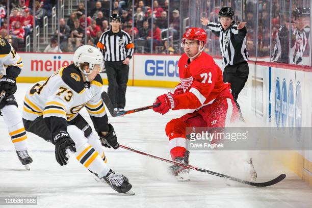 Dylan Larkin of the Detroit Red Wings shoots the puck past Charlie McAvoy of the Boston Bruins during an NHL game at Little Caesars Arena on February...