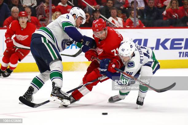 Dylan Larkin of the Detroit Red Wings tries to split the defense of Derrick Pouliot and Elias Pettersson of the Vancouver Canucks during the third...