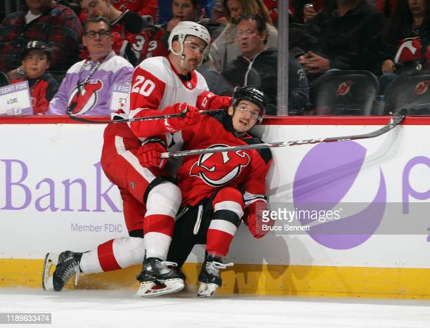 Dylan McIlrath of the Detroit Red Wings hits Brett Seney of the New Jersey Devils during the second period at the Prudential Center on November 23,...