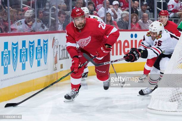Dylan McIlrath of the Detroit Red Wings skates with the puck behind the net followed by Zack Smith of the Chicago Blackhawks during a pre-season NHL...