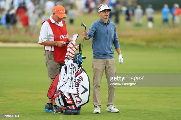 Dylan Meyer pulls a club from his bag as he prepares to play a shot on the eighth green as caddie Steve Hulka looks on during the second round of the...