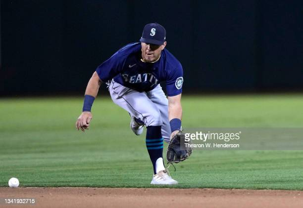 Dylan Moore of the Seattle Mariners goes down to field a ground ball off the bat of Mark Canha of the Oakland Athletics in the bottom of the seventh...