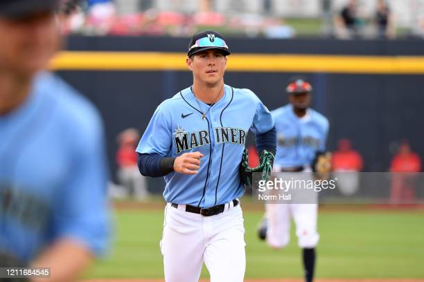 Dylan Moore of the Seattle Mariners runs to the dugout after the end of an inning against the Los Angeles Angels during a spring training game at...