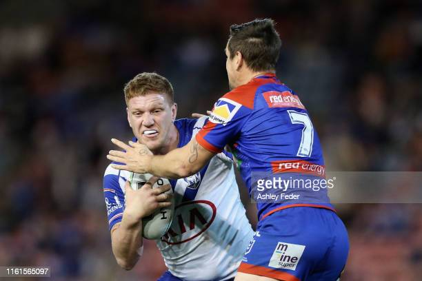 Dylan Napa of the Bulldogs is tackled by the Knights defence during the round 17 NRL match between the Newcastle Knights and the Canterbury Bulldogs...