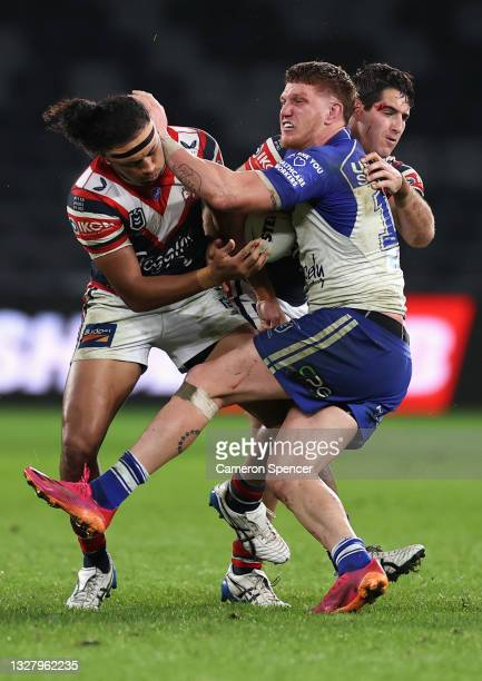 Dylan Napa of the Bulldogs is tackled during the round 17 NRL match between the Canterbury Bulldogs and the Sydney Roosters at Bankwest Stadium, on...