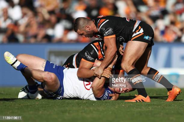 Dylan Napa of the Bulldogs is tackled during the round three NRL match between the Wests Tigers and the Canterbury Bulldogs at Campbelltown Stadium...