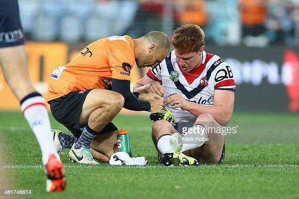 Dylan Napa of the Roosters is helped by a trainer as he tries to untie his boot during the round 20 NRL match between the Wests Tigers and the Sydney...