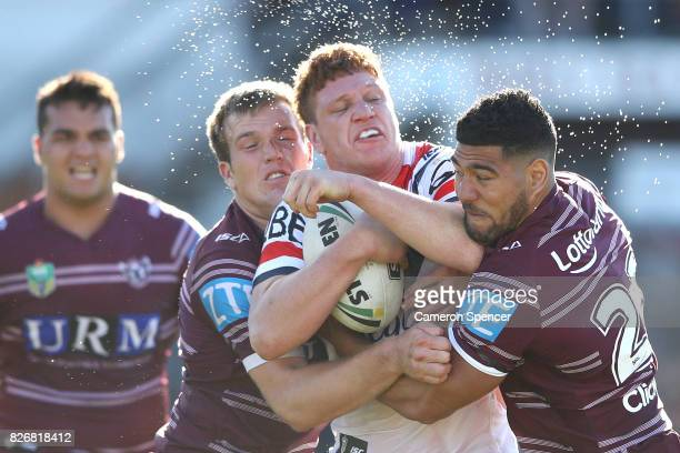Dylan Napa of the Roosters is tackled during the round 22 NRL match between the Manly Warringah Sea Eagles and the Sydney Roosters at Lottoland on...