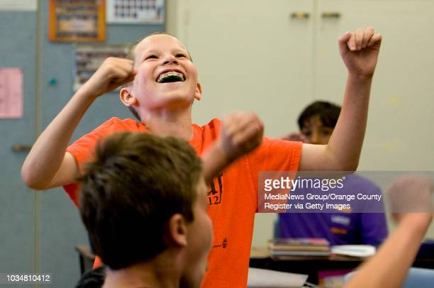 Dylan Oliver center celebrates after correctly answering a question during a California Gold Rush simulation quiz in Liz Ramos' fourth grade class at...