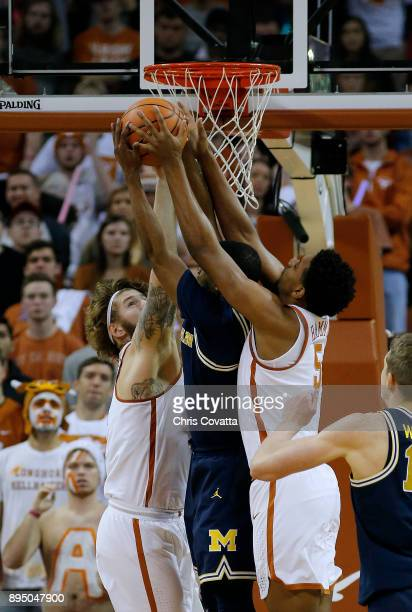 Dylan Osetkowski and Royce Hamm Jr #5 of the Texas Longhorns fight for a rebound with MuhammadAli AbdurRahkman of the Michigan Wolverines at the...