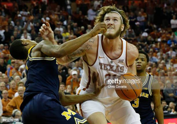 Dylan Osetkowski of the Texas Longhorns charges Charles Matthews of the Michigan Wolverines at the Frank Erwin Center on December 12 2017 in Austin...