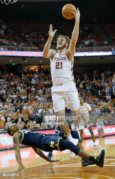 Dylan Osetkowski of the Texas Longhorns commits charge against Charles Matthews of the Michigan Wolverines as at the Frank Erwin Center on December...
