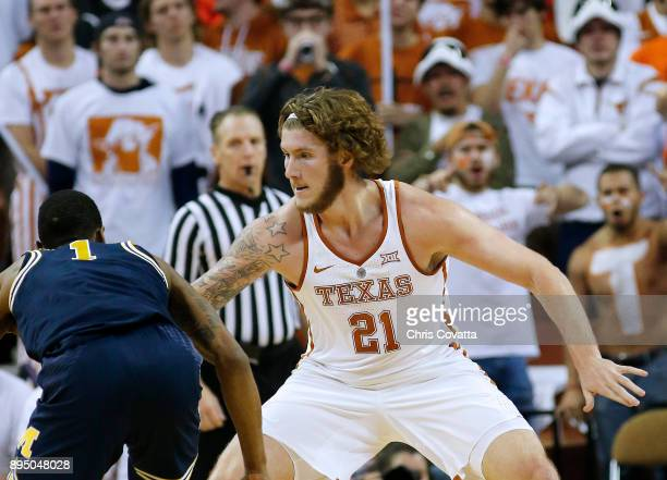 Dylan Osetkowski of the Texas Longhorns defends Charles Matthews of the Michigan Wolverines at the Frank Erwin Center on December 12 2017 in Austin...