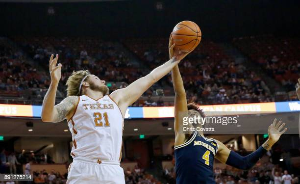 Dylan Osetkowski of the Texas Longhorns fights for a rebound against Isaiah Livers of the Michigan Wolverines at the Frank Erwin Center on December...