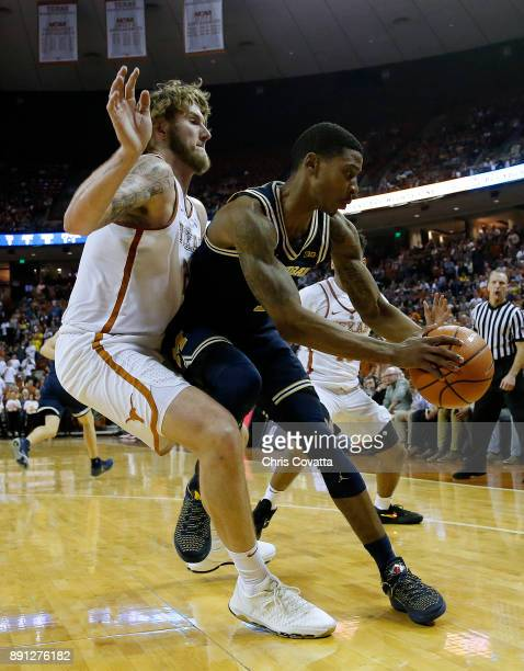 Dylan Osetkowski of the Texas Longhorns presses Charles Matthews of the Michigan Wolverines at the Frank Erwin Center on December 12 2017 in Austin...