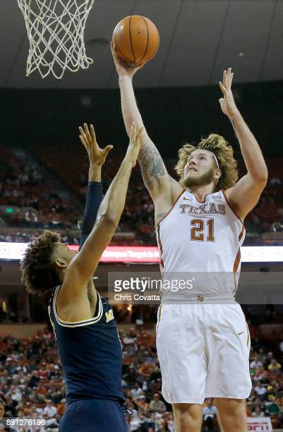 Dylan Osetkowski of the Texas Longhorns shoots over Isaiah Livers of the Michigan Wolverines at the Frank Erwin Center on December 12 2017 in Austin...