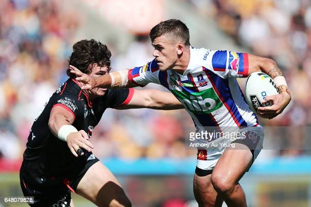 Dylan Phythian of the Knights on the charge against Charlie Gubb of the Warriors during the round one NRL match between the New Zealand Warriors and...