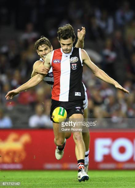 Dylan Roberton of the Saints kicks whilst being tackled by Tom Hawkins of the Cats during the round five AFL match between the St Kilda Saints and...