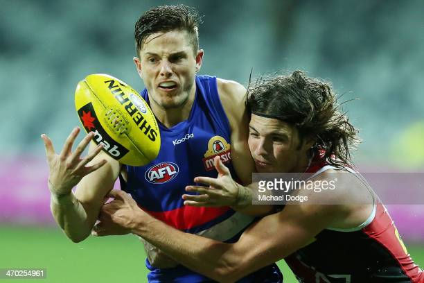 Dylan Roberton tackles Jason Tutt of the Bulldogs during the round two AFL NAB Challenge Cup match between the Western Bulldogs and the St Kilda...
