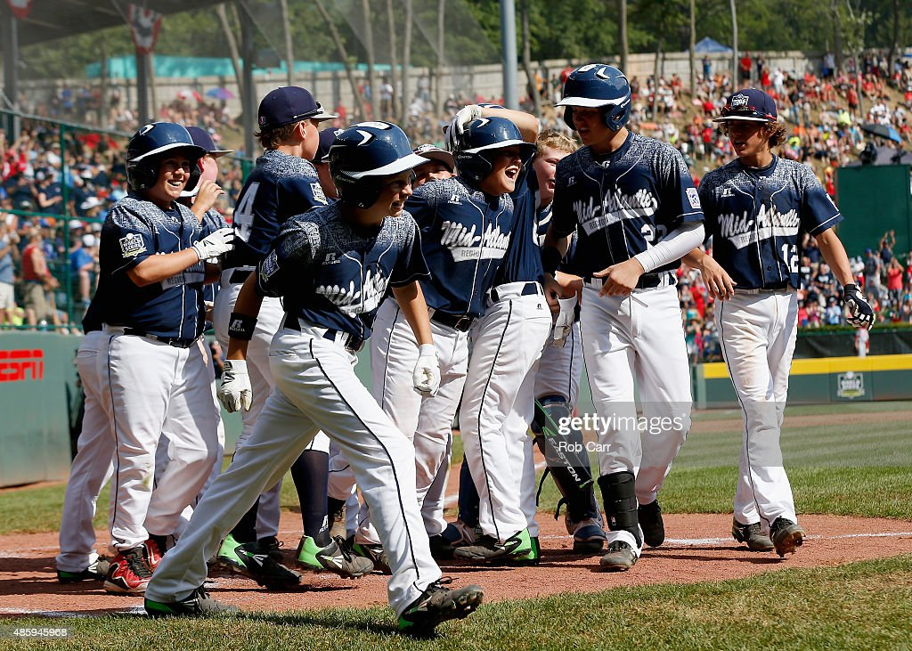 Dylan Rodenhaber #18 of the Mid-Atlantic team from Red Land Little League of Lewisberry, Pennsylvania (C) is mobbed by teammates after hitting a grand slam against team Japan in the first inning of the Little League World Series Championship game at Lamade Stadium on August 30, 2015 in South Willamsport, Pennsylvania.