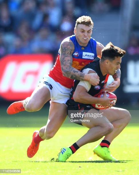 Dylan Shiel of the Bombers is tackled by Mitch Robinson of the Lions during the round four AFL match between the Essendon Bombers and the Brisbane...