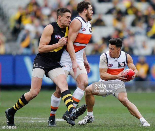 Dylan Shiel of the Giants runs with the ball being protected from Ivan Soldo of the Tigers by Shane Mumford during the round 18 AFL match between the...