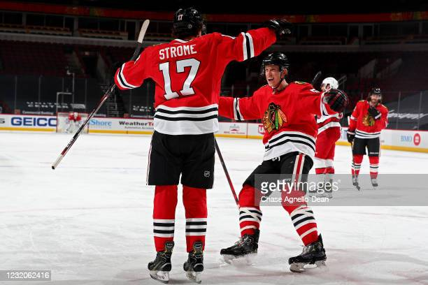 Dylan Strome and Connor Murphy of the Chicago Blackhawks celebrate after Strome scored a goal in the third period against the Carolina Hurricanes at...