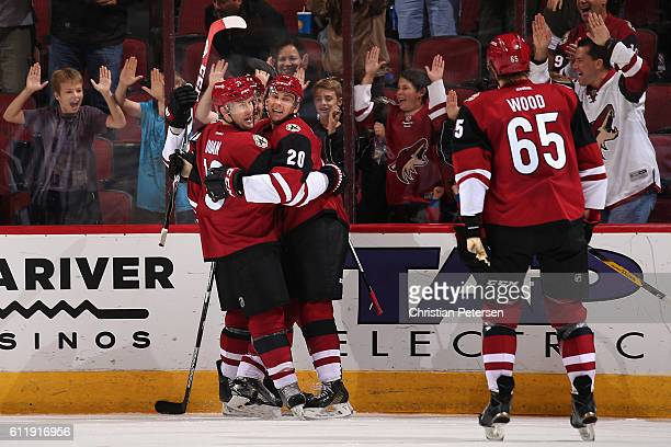 Dylan Strome of the Arizona Coyotes celebrates with Shane Doan and Kyle Wood after Strome scored a third period goal against Anaheim Ducks during the...