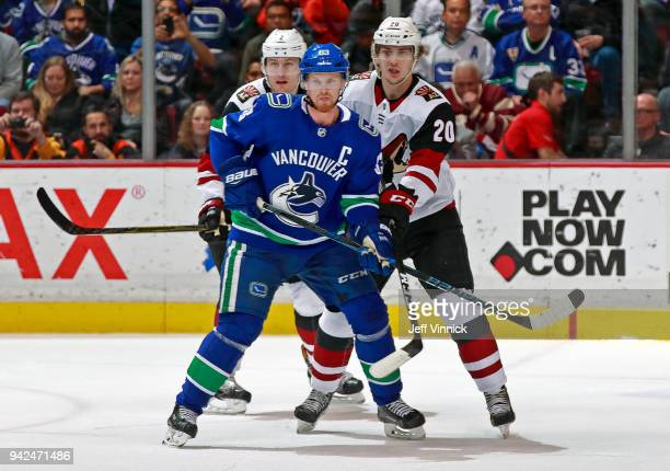 Dylan Strome of the Arizona Coyotes checks Henrik Sedin of the Vancouver Canucks during their NHL game at Rogers Arena April 5 2018 in Vancouver...