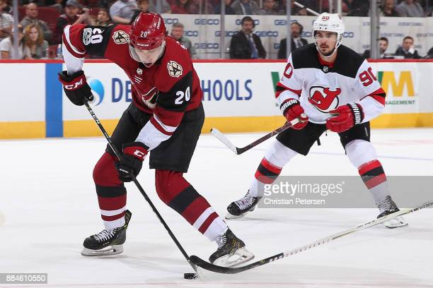 Dylan Strome of the Arizona Coyotes skates in with the puck to score his first career goal ahead of Marcus Johansson of the New Jersey Devils during...