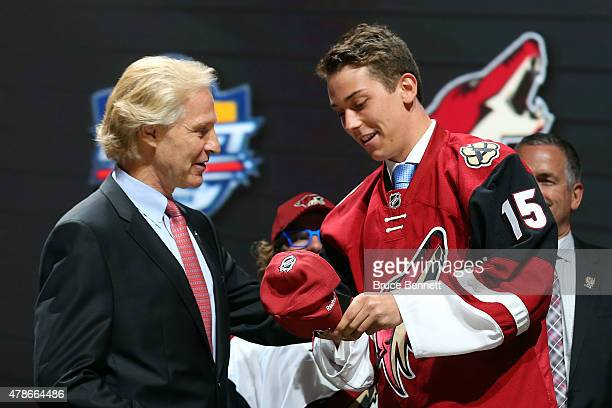 Dylan Strome puts on a hat after being selected third overall by the Arizona Coyotes in the first round of the 2015 NHL Draft at BBT Center on June...