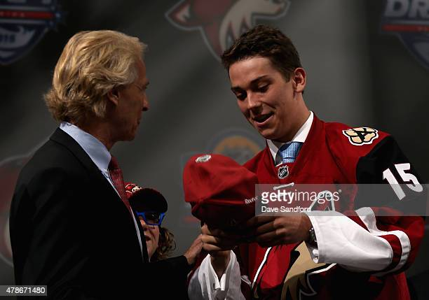 Dylan Strome puts on his hat after being selected third overall by the the Arizona Coyotes during Round One of the 2015 NHL Draft at BBT Center on...