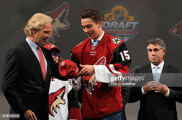 Dylan Strome puts on his hat prior to posing onstage with members of the Arizona Coyotes organization after being selected third overall by the the...