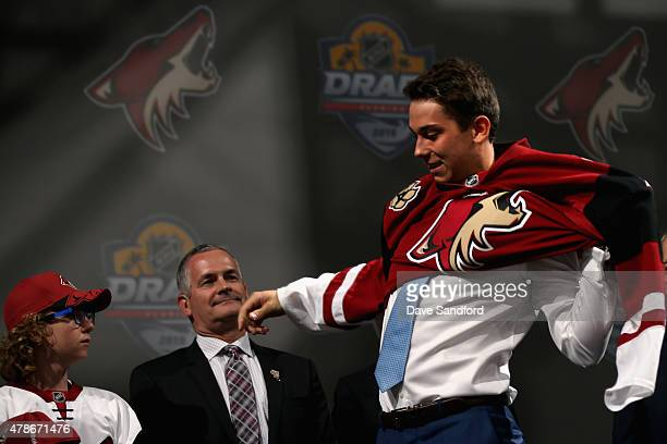 Dylan Strome puts on his jersey after being selected third overall by the the Arizona Coyotes during Round One of the 2015 NHL Draft at BBT Center on...
