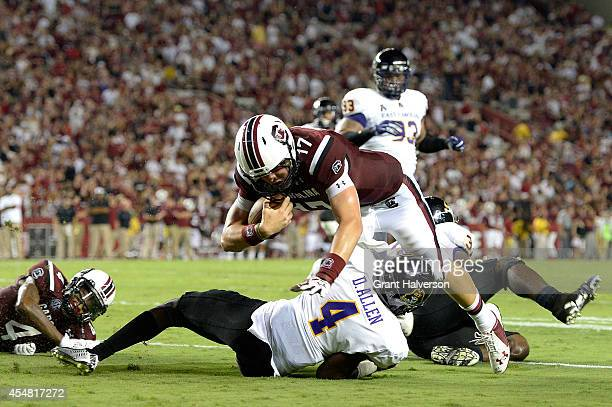 Dylan Thompson of the South Carolina Gamecocks dives over Malik Gray of the East Carolina Pirates as he reaches for the goal line during their game...
