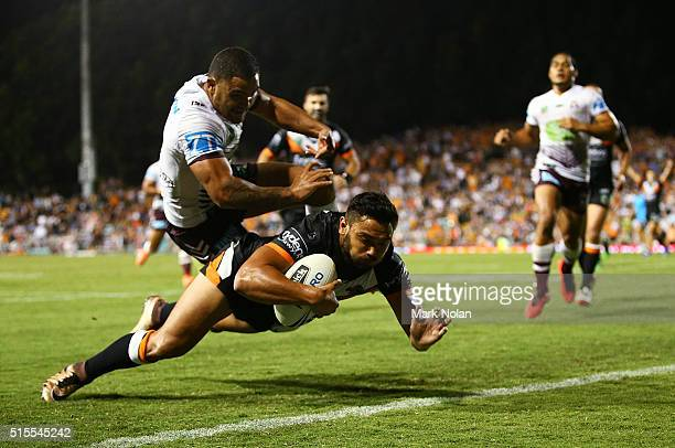 Dylan Walker of the Eagles attempts to prevent David Nofoaluma of the Tigers from scoring a try during the round two NRL match between the Wests...