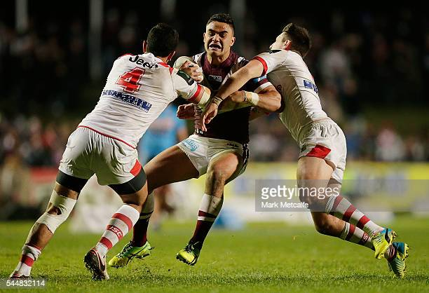 Dylan Walker of the Sea Eagles is tackled by Timoteo Lafai and Gareth Widdop of the Dragons during the round 17 NRL match between the Manly Sea...