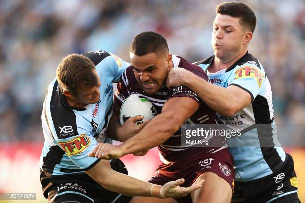 Dylan Walker of the Sea Eagles is tackled during the round 10 NRL match between the Cronulla Sharks and the Manly Sea Eagles at Shark Park on May 19,...