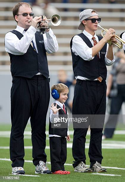 Dylan Welsh joins his father Erik left and other members of the Rice Marching Owl Band on the field for pregame festivities before the Owls faced...