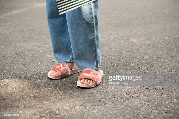 Dylan Xue wears a pink denim blue jeans and pink furry Puma sandals after the Ports 1961 show during Milan Fashion Week Spring/Summer 2017 on...
