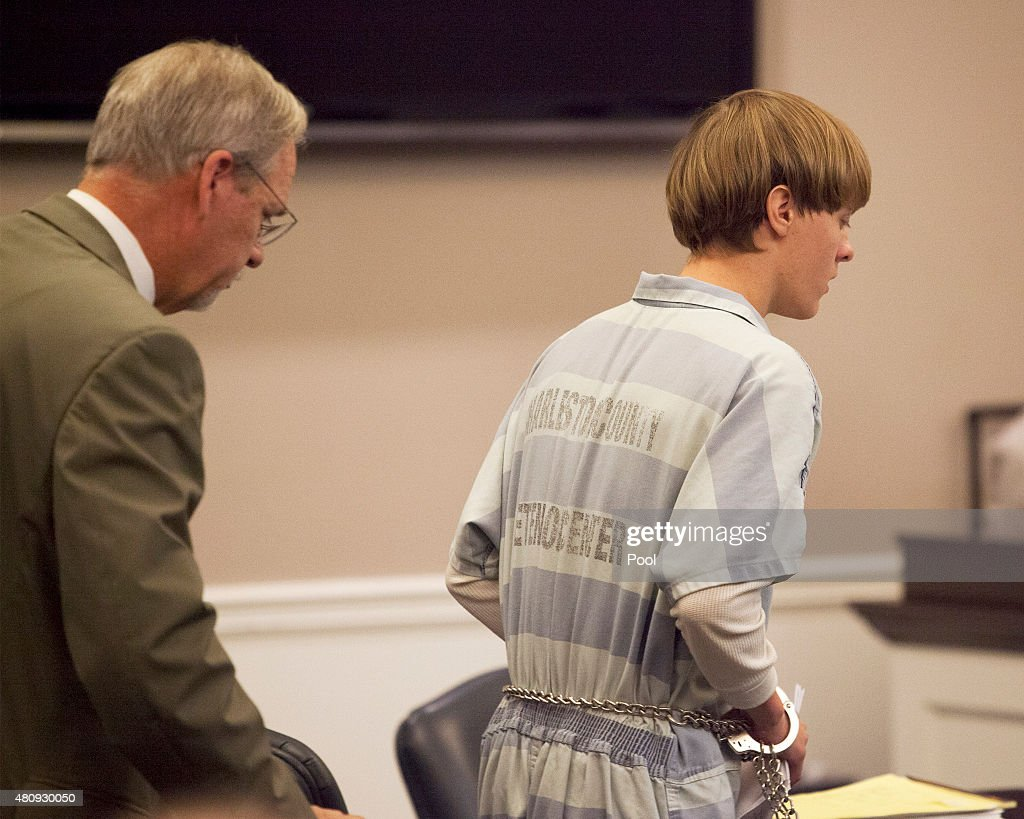 Dylann Roof (R), the 21-year-old man charged with murdering nine worshippers at a historic black church in Charleston last month, is helped to his chair by chief public defender Ashley Pennington during a hearing at the Judicial Center in Charleston : News Photo