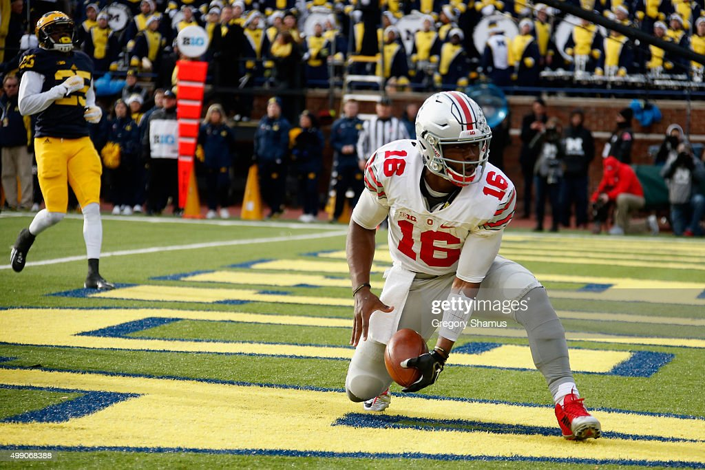 Dymonte Thomas #25 of the Michigan Wolverines looks on as quarterback J.T. Barrett #16 of the Ohio State Buckeyes celebrates after rushing for a third quarter touchdown at Michigan Stadium on November 28, 2015 in Ann Arbor, Michigan.