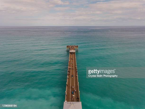 dynamic aerial views of colorful teal ocean waves sweeping across the juno beach, florida seashore & pier at mid-day in january of 2021 - juno beach florida stock pictures, royalty-free photos & images