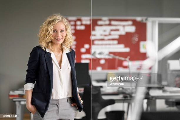 Dynamic businesswoman standing in office, smiling