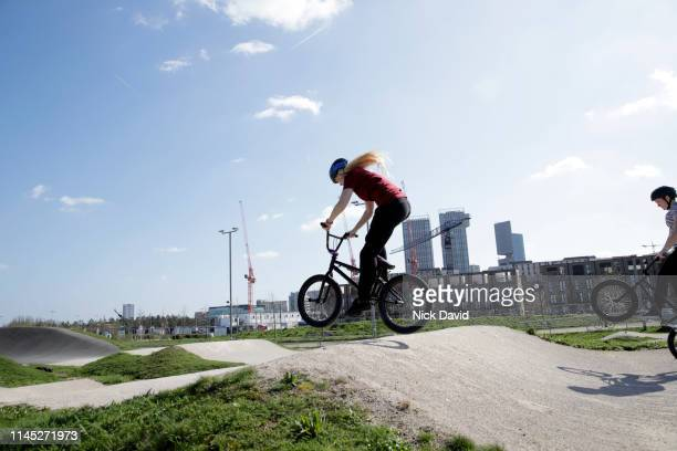 dynamic female cyclist in mid air on bmx track - parc olympique lieu photos et images de collection