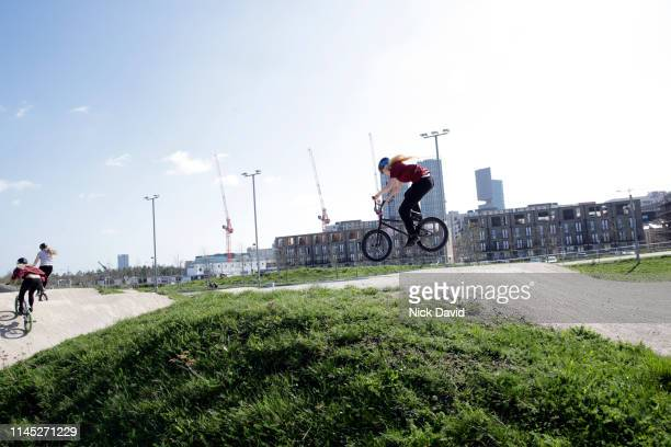 dynamic female cyclist jumping on bmx during race - bmx track london stock pictures, royalty-free photos & images