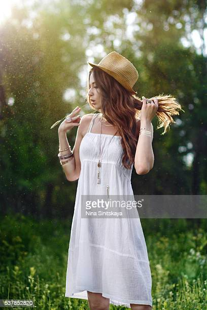 Dynamic hot woman in white dress and a hat standing in the grass during sunset